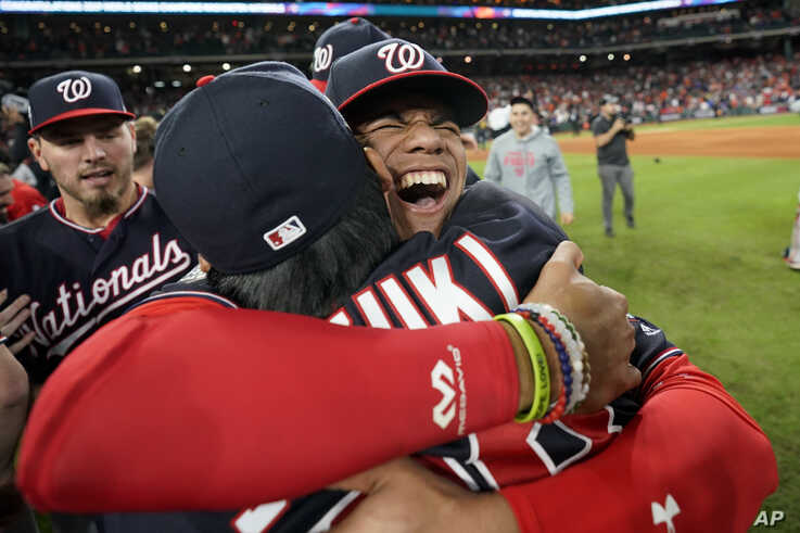 Washington Nationals left fielder Juan Soto, right, hugs catcher Kurt Suzuki after Game 7 of the baseball World Series against…