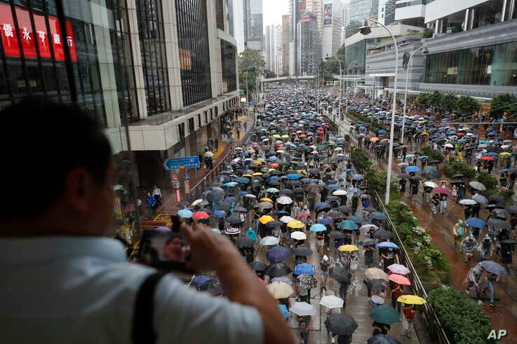 A man takes pictures as protesters wearing face masks and holding umbrellas march on a street in Hong Kong, Sunday, Oct. 6,…
