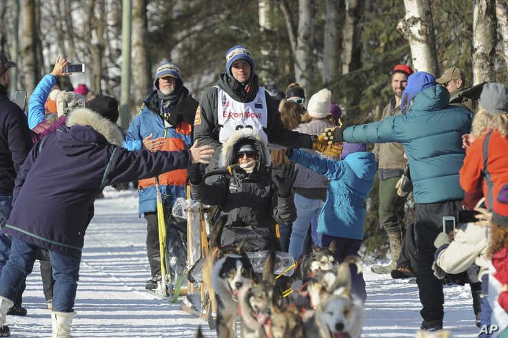 Defending Iditarod champion Joar Lefseth Ulsom, of Norway, greets fans on the trail during the ceremonial start of the Iditarod…
