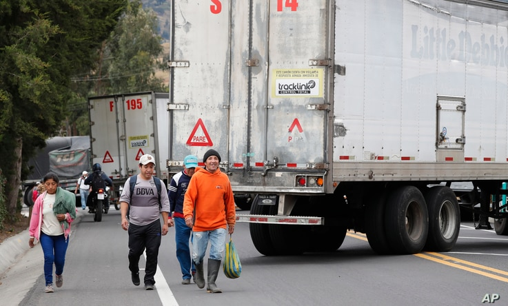 Residents walk along the Pan-American highway blocked by parked semi-trailer trucks during a nationwide transport strike that…