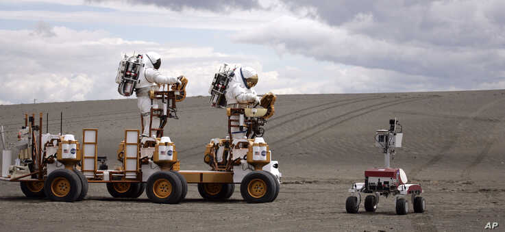 Two NASA astronauts in space suits drive their lunar truck near K-10 Red June 10, 2008, in Moses Lake, Wash.  NASA scientists…