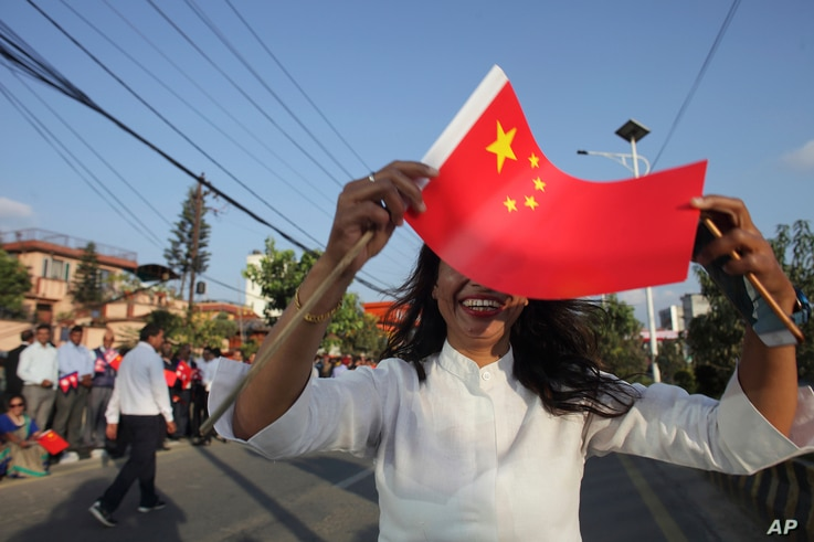 A woman holds a Chinese flag and stands by the side of a road to welcome Chinese President Xi Jinping in Kathmandu