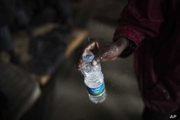In this photo taken Friday, Nov. 29, 2013, African migrants fills an empty bottle with leaking water from the roof of a barrack…