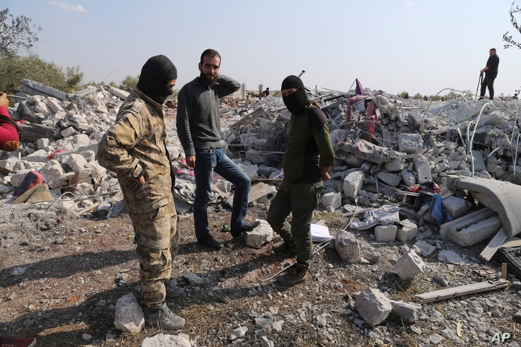 People look at a destroyed houses near the village of Barisha, in Idlib province, Syria, Oct. 27, 2019