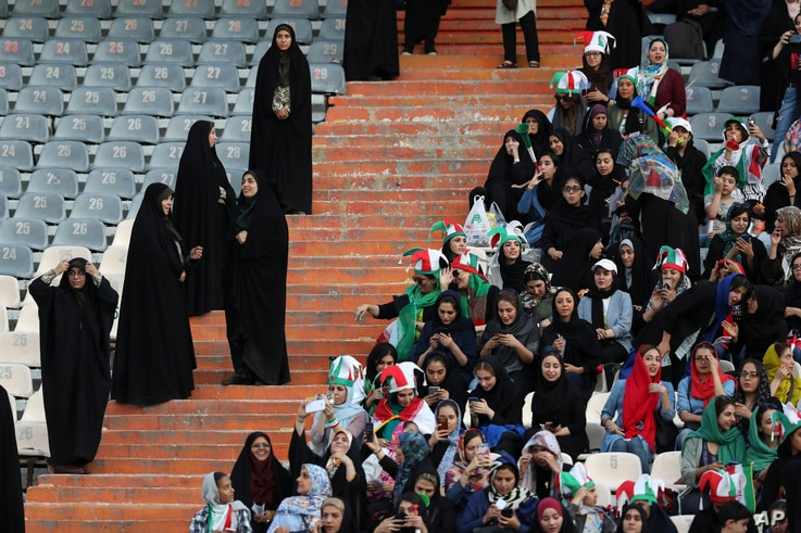 Iranian women follow the 2022 World Cup qualifier soccer match between Iran and Cambodia as female police officers stand, left,…