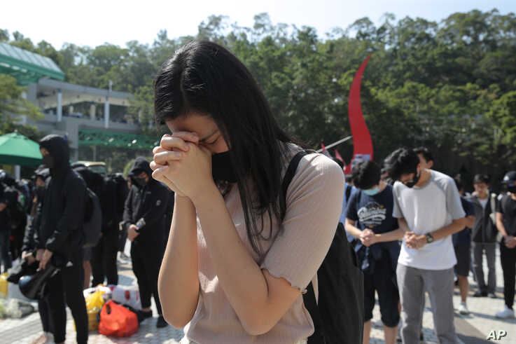 Protesters pause for a moment of silence after disrupting a graduation ceremony at the University of Science and Technology and…