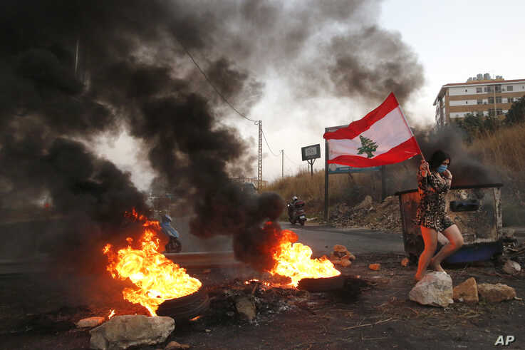 An anti-government protester carries her national flag past burning tires blocking the main highway during protests against the…