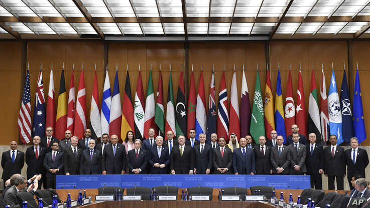 Secretary of Sate Mike Pompeo, center, and other foreign ministers and foreign officials pose for a family photo at the State…