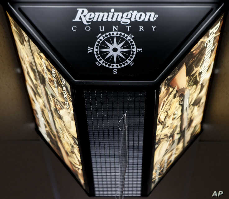 FILE - In this March 1, 2018 file photo, a light advertising Remington products hangs from the ceiling at Duke's Sport Shop in…