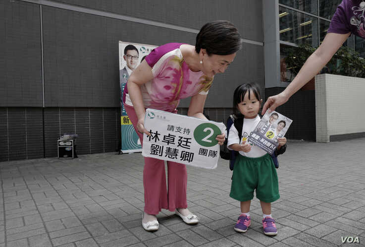 In this Wednesday, Aug. 24, 2016 photo, Hong Kong pro-democracy lawmaker, Emily Lau talks to a girl during a election campaign…
