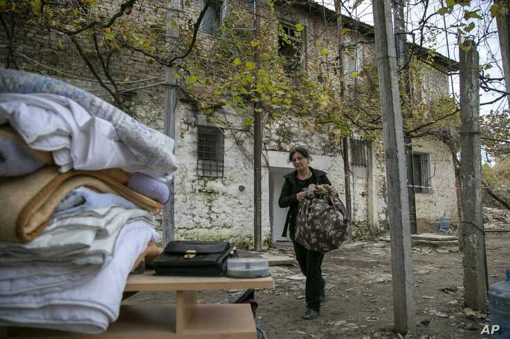 A woman carries her belongings from a damaged house in Thumane, western Albania, Friday, Nov. 29, 2019. The operation to find…