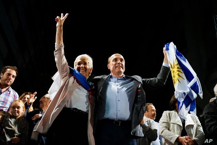 Presidential candidate for the ruling party Broad Front Daniel Martinez, right, and Graciela Villar, his running mate, wave to…