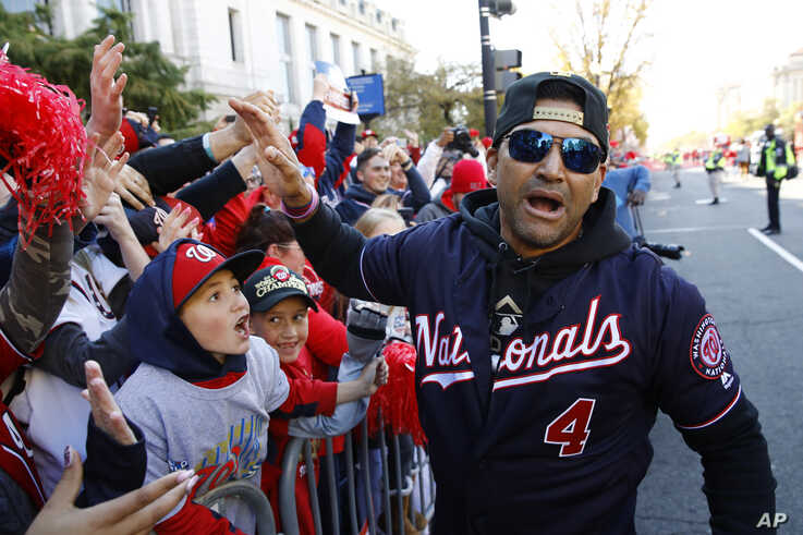 Washington Nationals manager Dave Martinez celebrates with fans during a parade to celebrate the team's World Series baseball…
