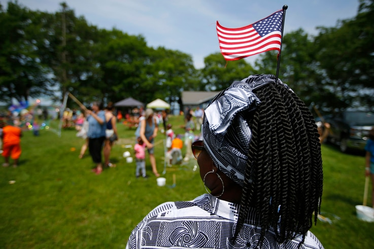 FILE - In this July 4, 2019, file photo, Malu Klo, an asylum seeker from the Congo, attends a picnic for refugees at Fort…
