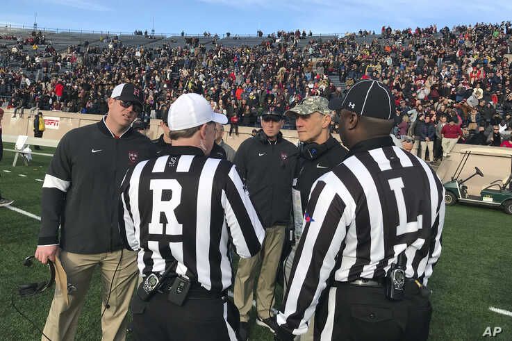 Harvard coach Tim Murphy, second from right, speaks with officials as demonstrators stage a protest on the field at the Yale…