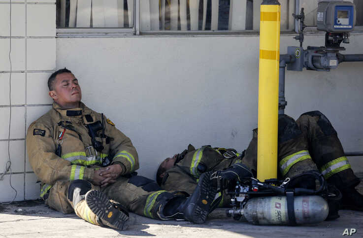 Firefighters rest at outside a cardboard box factory that burned down by a wildfire in Riverside, Calif. Thursday, Oct. 31,…