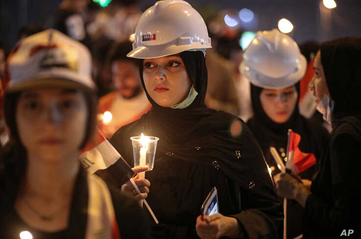 Iraqi women light candles for slain anti-government protesters during ongoing protests in Basra, Iraq, Friday, Nov. 29, 2019. …