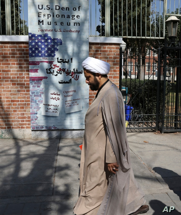 In this Tuesday, Oct. 15, 2019 photo, a Shiite Muslim cleric walks past anti-U.S. graffiti on the wall of the former U.S…