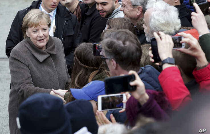 German Chancellor Angela Merkel, left, shakes hands with visitors prior to a memorial service in the chapel at the Berlin Wall…