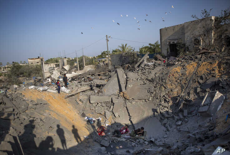 Palestinians sit amid the rubble of their destroyed house following overnight Israeli missile strikes, in the town of Khan…