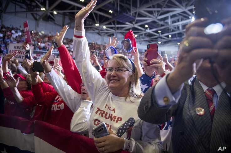 Members of the audience wave and cheer as President Donald Trump speaks at a rally at BancorpSouth Arena in Tupelo, Miss.,…