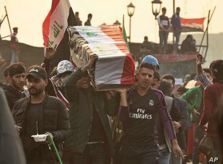 Anti-government protesters carry a symbolic coffin during ongoing protests in Baghdad, Iraq, Friday, Nov. 29, 2019. Hundreds of…