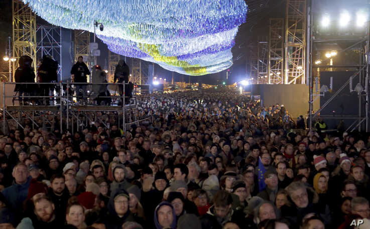Visitors stay underneath the skynet artwork 'Visions In Motion' in front of the Brandenburg Gate as they attend stage…