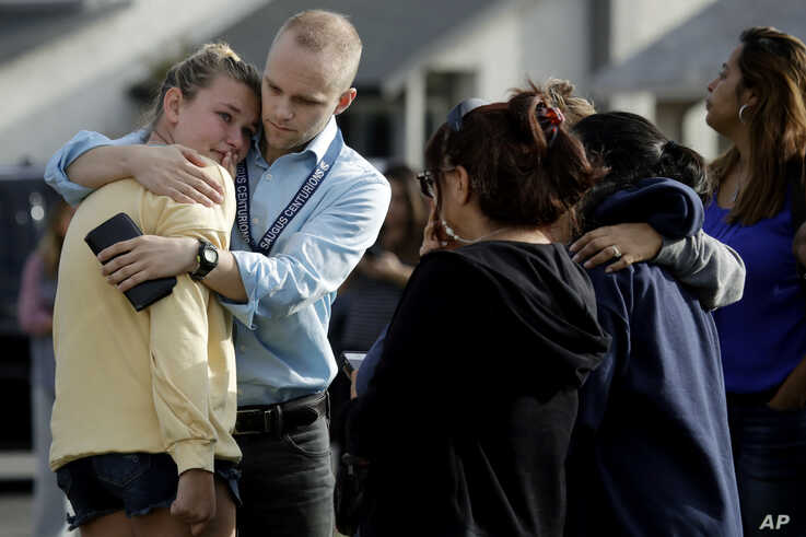 D.J. Hamburger, center in blue, a teacher at Saugus High School, comforts a student after reports of a shooting at the school…