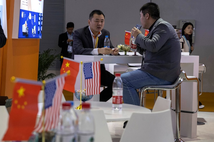 In this photo taken Wednesday, Nov. 6, 2019, visitors chat near American and Chinese flags displayed at a booth for an American…