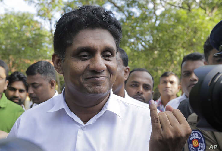 Presidential candidate of Sri Lanka's governing party Sajith Premadasa displays the indelible ink mark on his finger after…