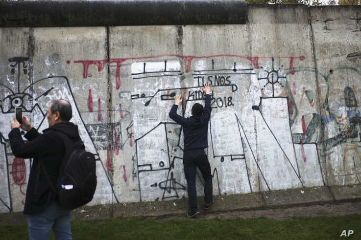 Tourist take photos at remains of the Berlin Wall after commemorations celebrating the 30th anniversary of the fall of the…