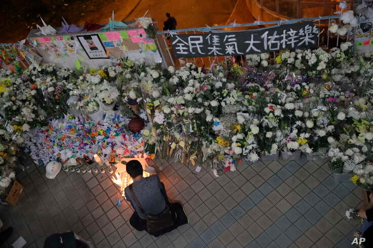 """A protester light candles near flowers and a banner which reads """"From all of us - God bless Chow Tsz-Lok"""" at the site where…"""