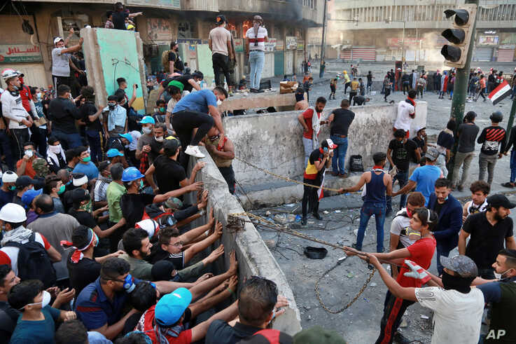 Protesters try to pull down concrete walls placed by Iraqi security forces during clashes between Iraqi security forces and…