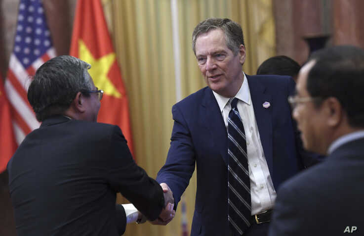 U.S. Trade Representative Robert Lighthizer, center, shakes hands with Vietnamese Ambassador to the U.S. Pham Quang Vinh  as…