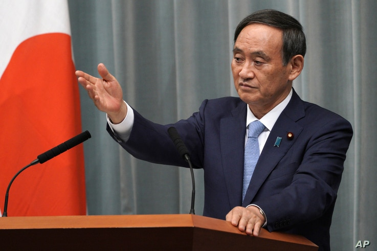 FILE - In this Sept. 11, 2019, file photo, Yoshihide Suga, Chief Cabinet Secretary speaks during a press conference at the…