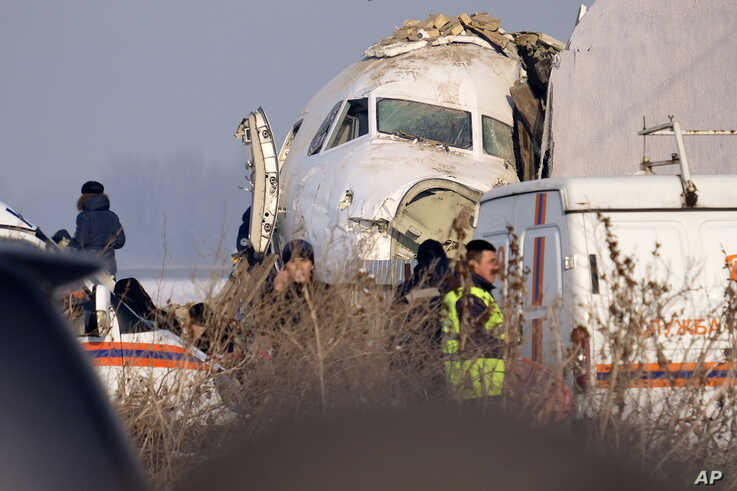Police stand guard as rescuers assist on the site of a plane crashed near Almaty International Airport, outside Almaty,…
