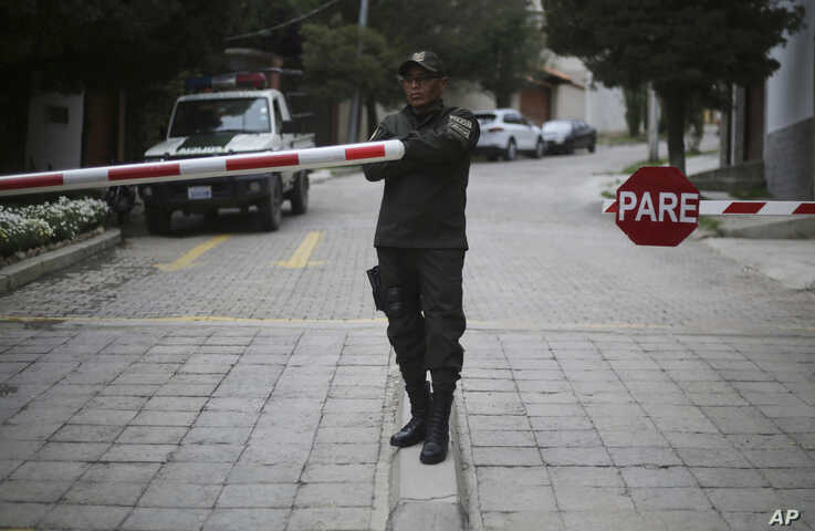 A police officer stands at the entrance leading to the residence of Mexico's ambassador to help make sure nine former officials…