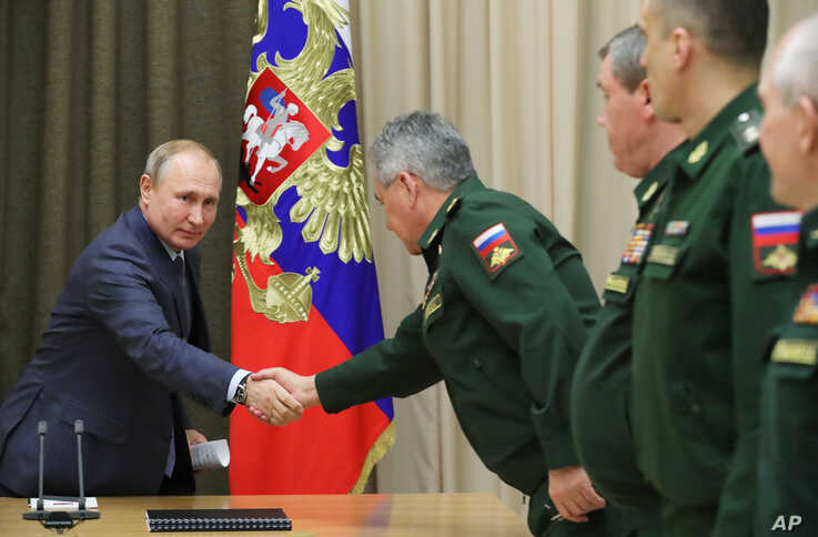 Russian President Vladimir Putin, left, and Russian Defense Minister Sergei Shoigu, center, shake hands during with military…