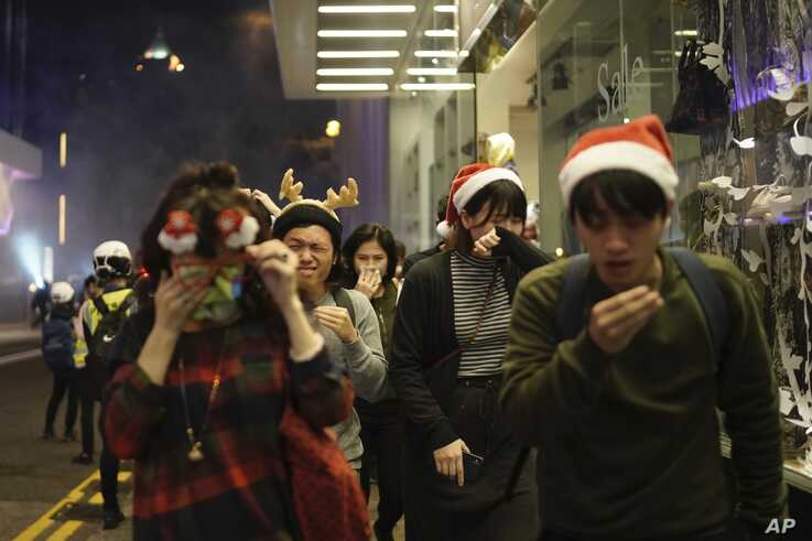 Residents dressed for Christmas festivities react to tear gas as police confront protesters on Christmas Eve in Hong Kong on…
