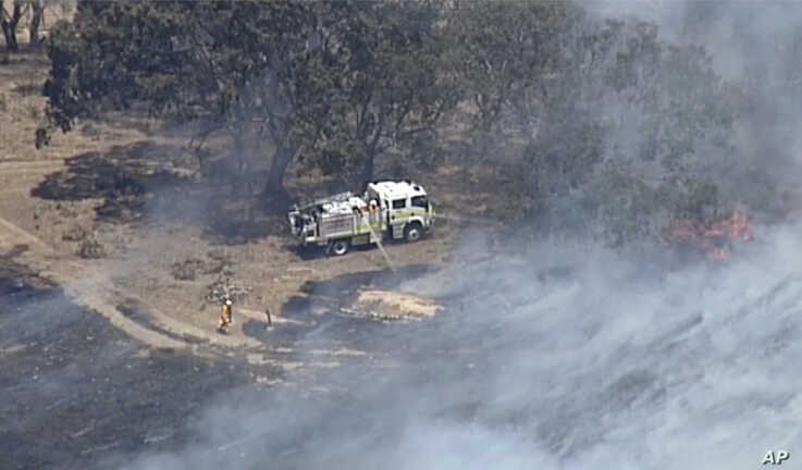 In this image made from video, an aerial scene shows firefighters extinguishing wildfires in the Adelaide Hills, Australia,…
