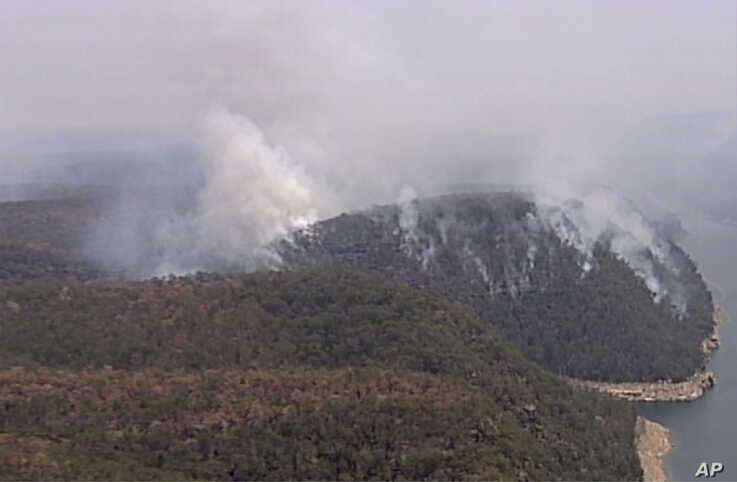 In this image made from video, smoke rises from wildfires Friday, Dec. 27, 2019, in the Blue Mountains, New South Whales,…