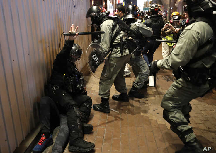 Riot police detain a protester, left lying on the ground, during a demonstration in Hong Kong, Wednesday, Dec. 25, 2019…