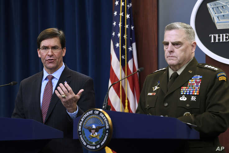 Defense Secretary Mark Esper, left, standing with Joint Chiefs Chairman Gen. Mark Milley, right, speaks during a news…