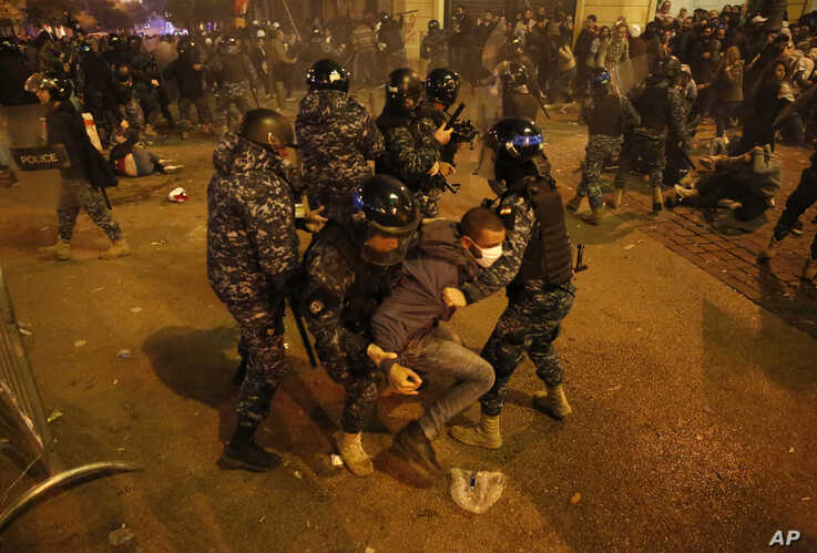 Riot police officers beat anti-government protesters during a protest near the parliament square, in downtown Beirut, Lebanon,…