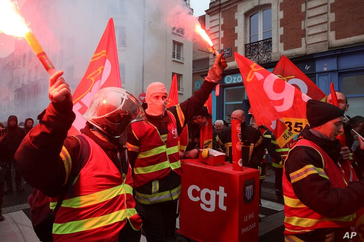 Firefighters hold flares during a protest in Rennes, western France