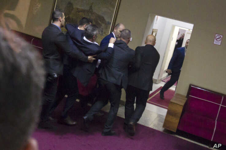 Police officers carry a pro-Serb opposition lawmaker in the parliament building in Podgorica, Montenegro, Friday, Dec. 27, 2019…