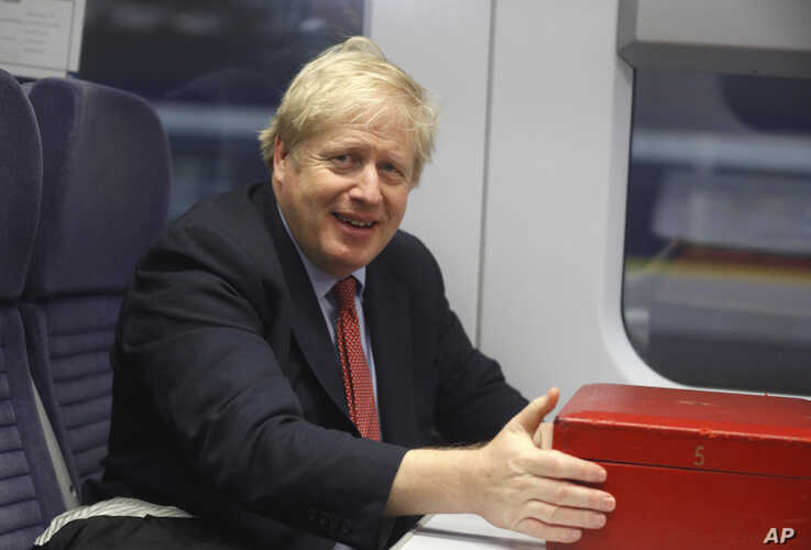 Britain's Prime Minister Boris Johnson sits on a train in London, Friday Dec. 6, 2019, on the campaign trail ahead of the…