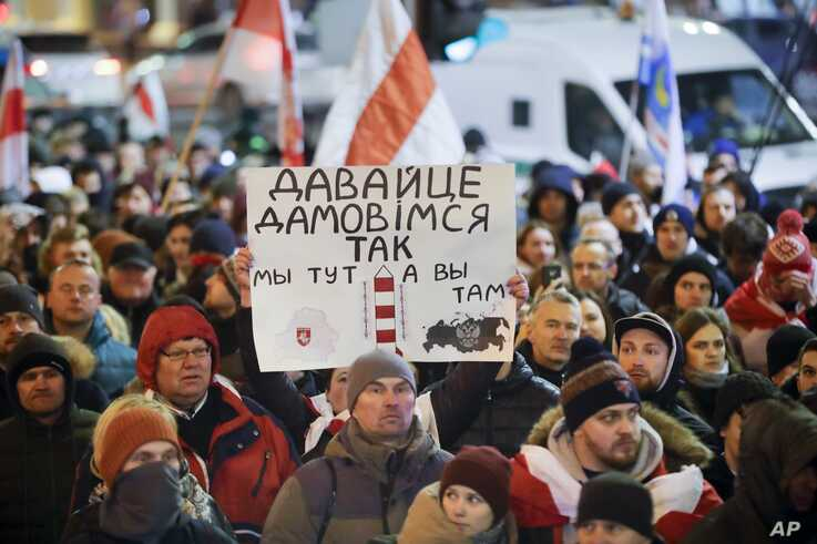 """Demonstrators carry a poster reads """"let's agree so we're here, you're there"""" during a march to protest closer integration with…"""