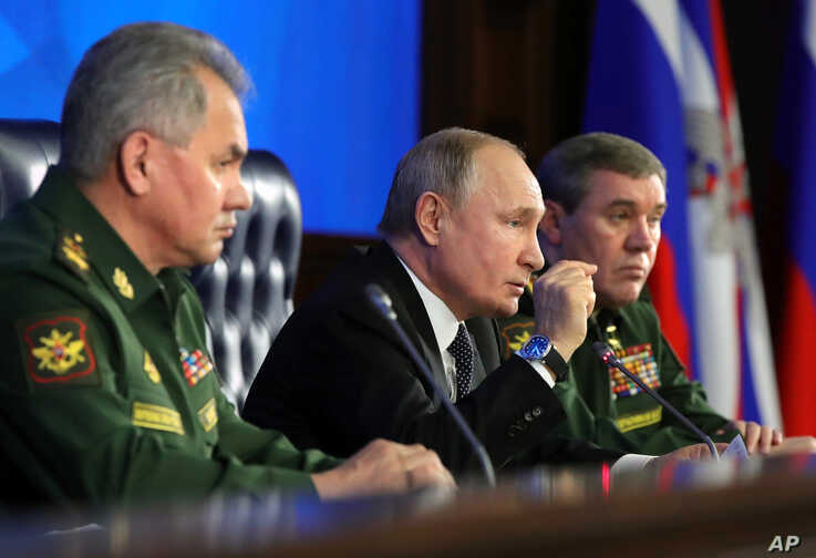 Russian President Vladimir Putin, center, gestures while speaking during an annual meeting with top military officials in the…