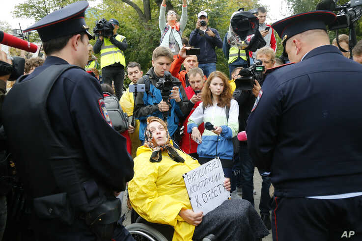 """In this Saturday, Aug. 17, 2019 photo, A wheelchair bound woman activist surrounded by journalists holds a poster reading """"The…"""